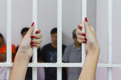 Woman fingers with red nails. Woman fingers with red nails holding grip on the bars of the cage with the accused Royalty Free Stock Images