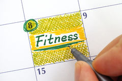 Woman fingers writing reminder Fitness in calendar. Close-up Royalty Free Stock Photography