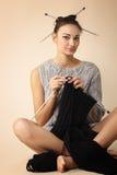 Woman finish knitting sweater. Isolated on beige background Royalty Free Stock Photo