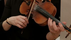 The woman finishes playing the violin and removes the musical instrument from the shoulder. Close-up. Right female hand with a rin stock video
