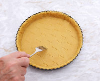 Woman finishes pricking holes in a pastry pie crust Stock Images