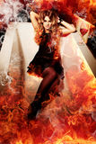 Woman in fire bath. With a glass of red wine Stock Images