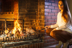 Woman with fire iron poker at home fireplace. Royalty Free Stock Image