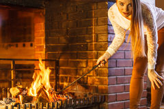 Woman with fire iron poker at home fireplace. Stock Images