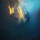 Woman on fire underwater Stock Photo