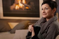Woman at fireplace Stock Images