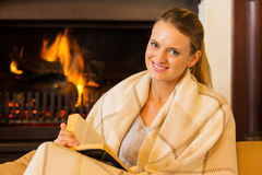 Woman fireplace book Stock Photos