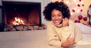 Woman by fireplace and wearing warm sweater stock video