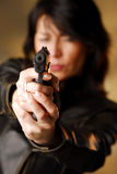 A woman firing from a gun Stock Images