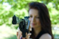 Woman firing with pneumatic gun. Focus on gun point Royalty Free Stock Image
