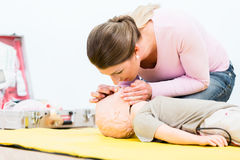 Woman in first aid course practicing revival of infant on baby d royalty free stock image