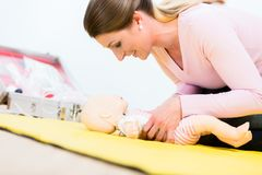 Woman in first aid course practicing revival of infant on baby d. Oll royalty free stock photography
