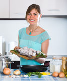 Woman with fish and frying pan at kitchen Royalty Free Stock Photos