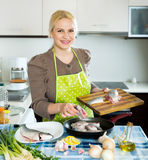 Woman with fish in pan Stock Images