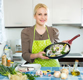 Woman with fish in pan Royalty Free Stock Photography