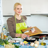 Woman with fish in pan Royalty Free Stock Photo