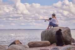 Woman fisher sitting. On beach with dogs Stock Photography