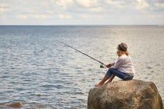 Woman fisher. Sitting on summer sea beach royalty free stock photo