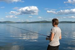 A woman fisherman catches fish for a bait from a blue lake on the background of a mountainous coast. Bright shot. Bright shot. A woman fisherman catches fish for stock photography