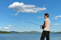 Woman fisherman catches a fish from a blue lake against a blue sky with clouds. Bright shot. Bright shot. Woman fisherman catches a fish from a blue lake against royalty free stock photo