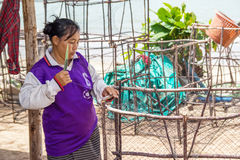 Woman fishermen is weaving  fish-trap Royalty Free Stock Images