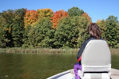Woman Fishing from a Boat. Woman doing some Autumn fishing from a boat royalty free stock image