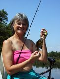 Woman fishing from a boat wih a fish. Woman holding a fish sitting in a boat against a lake and sky background stock photos