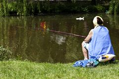 Woman fishing in a city park Stock Photo