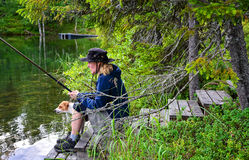 Woman fishing with dog Stock Image