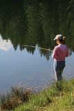 Woman fishing in lake. Rear view of woman fishing in lake with trees reflected in water Stock Image