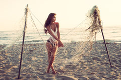 Woman and fishing net. Attractive young woman stand on sandy beach by fishing net at sunset full body shot stock photography