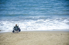 Woman fishing in the ocean. A woman sitting on a seat fishing at the edge of the ocean. Great for articles on fishing and gender Royalty Free Stock Image