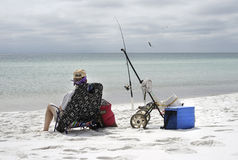 Woman Fishing on Overcast Day at the Beach royalty free stock photos