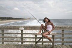 Woman fishing on the pier Stock Photography