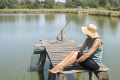 Woman fishing on pier Stock Photo