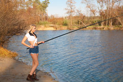 Woman fishing in river. Pretty girl in shorts with a fishing rod fishing on the sandy shore of the autumn river Royalty Free Stock Photos