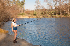Woman fishing in river. Pretty girl in shorts with a fishing rod fishing on the sandy shore of the autumn river Royalty Free Stock Photography