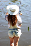 Young woman with summer sprouts and dungarees while fishing Royalty Free Stock Photos