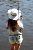 Young woman with summer sprouts and dungarees while fishing Royalty Free Stock Photo