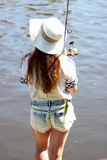 Young woman with summer sprouts and dungarees while fishing Royalty Free Stock Photography