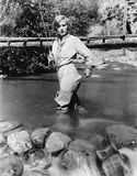 Woman with a fishing rod standing in the water stock photos