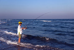 Woman fishing on a spinning, Florida, USA. Woman fishing at sunset on Gulf of Mexico, Florida, USA Stock Photo