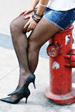 Woman in fishnets by hydrant Royalty Free Stock Image