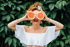 Woman fit girl holding two halfs of grapefruit. Citrus fruit in hands, covering her eyes on green background. Healthy diet food. Happiness holidays fun concept royalty free stock photo