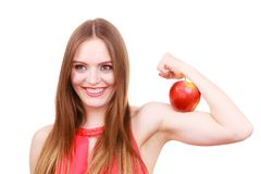 Woman fit girl holds apple fruit on her biceps arm. Woman young fit female long haired colorful make up holds big red apple fruit on her biceps arm. Healthy Royalty Free Stock Photo