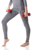 A woman fit legs, body, hands in gray sports thermal underwear doing exercises using red dumbbells. Stock Photography