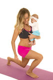 Woman in fitness attire lunge holding baby Royalty Free Stock Image