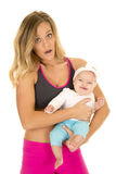 Woman  in fitness attire stand holding baby Royalty Free Stock Photography