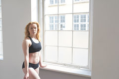 Woman in fitness attire standing by a window Stock Photos