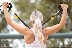Woman fitness. Back view of young attractive woman doing upper body exercise training arms using trx suspension straps outdoor alone Royalty Free Stock Image